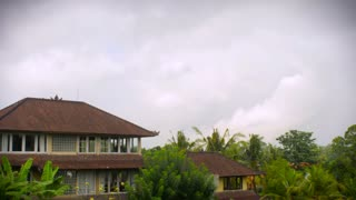 Time lapse of white fluffy full clouds in a blue sky with green tropical trees and traditional Balinese rooftops in the background.