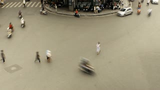 Time lapse with slow shutter speed of busy busy intersection in Hanoi, Vietnam where cars, scooters, and people work together without any traffic lights, or rules.