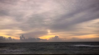 Timelapse of a ocean waves and sunset as the clouds approach the camera in Bali, Indonesia