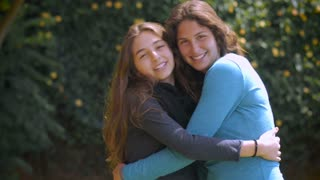 Two beautiful teenage girl friends with long brunette hair hug, smile and laugh in slow motion
