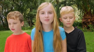 Two brothers and a sister look at the camera and goof around - slowmo. The oldest sister gently punches her brother and they laugh.