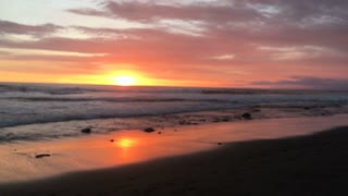 Two glasses of champagne clink and then pull away against a magnificent sunset on the beach