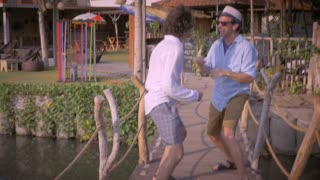 Two middle aged men friends having fun together on a wooden bridge in a tropical setting