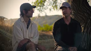 Two middle aged men sit together outside in the wilderness and talk during sunrise, or sunset while on a camping trip or hike in the woods as one of the men point to see something in the distance.