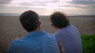 Two middle aged men sitting together and watching the sunset while talking with each other in slow motion.