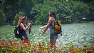 Two young attractive 20 something millennial travelers stand in front of a lake with colorful flowers in the foreground taking photographs of one another with a camera as tourists while wearing their traveling backpacks .