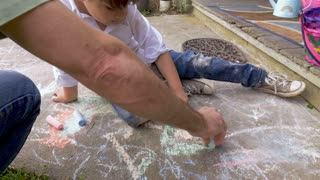 4-5 year old boy drawing with chalk with his dad using his left hand outside in slow motion