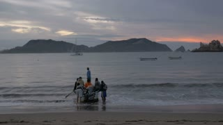 7 men get into a small motor boat from shore and go out towards sea during sunrise
