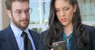 A attractive well dressed woman in business clothing shows a handsome millennial man in his 30s her smart phone social media social networking or video app while smiling and laughing outside