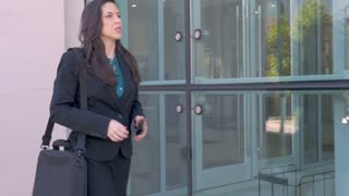 A beautiful female business executive shows her male business colleague her smart phone technology outside a glass office building in slow motion