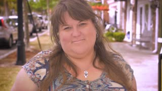 A beautiful happy attractive overweight woman smiling for the camera in slow motion outside a modern neighborhood shopping center