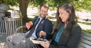 A beautiful woman and man eating healthy food and flirting, laughing, and smiling with each other outside on a park bench hand held in 4k