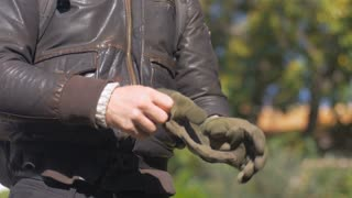 A caucasian man puts his bare hand into a motorcycle riding glove with his other hand that is already wearing a glove