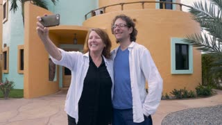 A couple take photos of themselves in front their new house with their cell phone and look at the photos together.