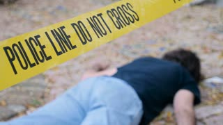 A dead murdered killed body roped off with Police Line Do Not Cross tape at crime scene - rack focus