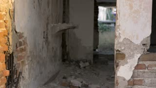 A destroyed hotel room with crumbling walls, brick, and floors from a major earthquake - dolly shot