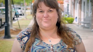 A disappointed full figured woman gives two thumbs down outside on a city sidewalk