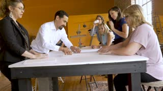 A diverse mostly young female business team revealing architectural blueprints for a new business building in slow motion