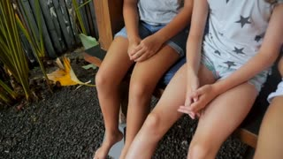 A group of young girls laps, legs and feet sitting next to each other - stabilized shot slow motion