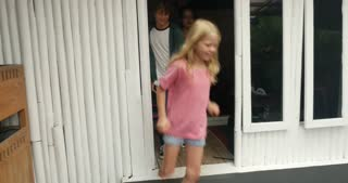 A group of young happy children running out of a doorway playing, laughing, and having fun