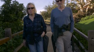 A happy active mature 60s couple walking outdoors on urban greenway. Retired husband and wife enjoying nature on path in an upscale neighborhood.