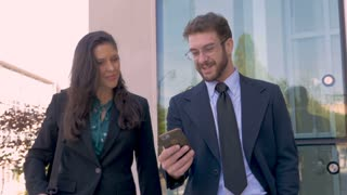 A happy businessman turning his smart phone horizontally to view mobile app video with a laughing businesswoman outside a contemporary business office complex in slow motion