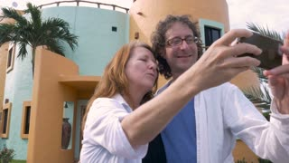 A happy older middle aged couple take selfies in front of their new house and look at the photos on their smart phone and smile.