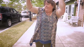 A large woman jammin out celebrating that she won something in slow motion on a city sidewalk