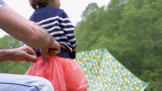 A man helps his daughter holding an umbrella get dressed pulling up her skirt outside looking up towards the trees in slow motion