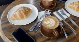 A man's hand takes a smart phone off a breakfast table with latte coffees and almond croissants