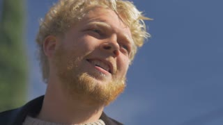 A millennial blond haired bearded man smiling against the blue sky - room for text