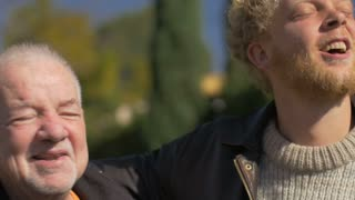 A millennial blond man and an elderly senior talking and embracing outside with their arms on each other's shoulders in the fall or early spring. The older man looks like he is giving advice or saying goodbye.
