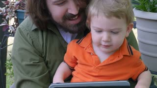 A millennial dad with a beard teaching his young baby boy how to use a tablet app or video technology outside.