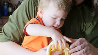 A millennial father with a beard watches intently as his young son feeds himself a healthy banana snack