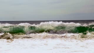 A powerful large wave crashes immediately off shore on to land in slow motion