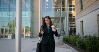A professional business woman in her 30s walking and using sms texting smartphone technology app with a to go coffee cup in front of a modern office building in 4k
