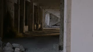 A ruined hallway and staircase from damage during an earthquake with crumbling bricks, and debris - dolly shot