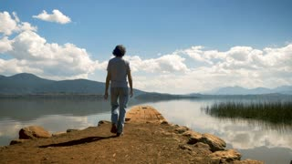 A single traveling man walks to the edge of a old pier overlooking a mountain lake