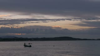 A small fishing boat sails past pelicans during sunrise or sunset on an ocean or lake
