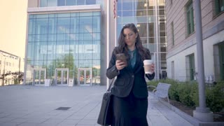 A successful millennial businesswoman executive walking away from a modern office building using smartphone technology app drinking togo coffee slow motion stabilized shot