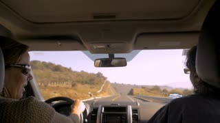 A woman driving with a male passenger talking and having a good time in a car on a road trip on a highway with no traffic
