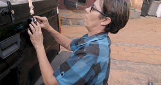 A woman in her 40s with short black hair prepares to install a lock on a truck tailgate