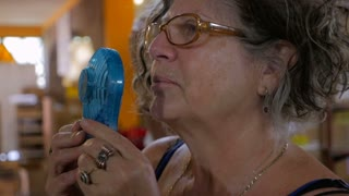 A woman in her early 60s holds a fan in front of her face to cool off on a hot summer day in slow motion