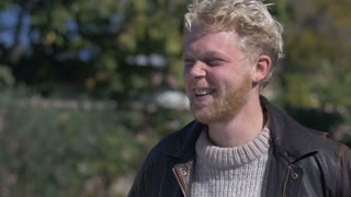 A young blond man with a beard has a genuine moment laughing and smiling at the camera outside wearing an open leather jacket and sweater in the fall or spring