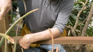 Active attractive senior man hammering a piece of wood into a metal brace during a remodeling project