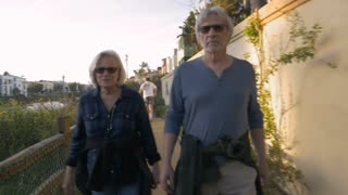 Active healthy happy attractive mature 60s adults walking in upscale neighborhood. Retired elderly caucasian couple exercising on urban greenway. Baby boomers on vacation exploring canals near Venice, California