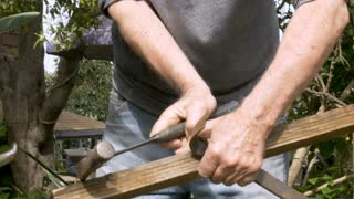 Active retired senior man reusing an old piece of wood removing rusty nails to fix a fence at his home
