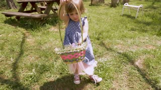 Adorable 2 - 3 year old girl in spring dress holding an easter basket filled with easter eggs in slow motion