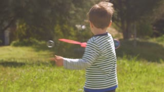 Adorable little boy spinning in circles making bubbles outside in a park on a lawn in slow motion