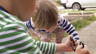 Adorable young boy and girl making colorful arts and crafts project outside in slow motion